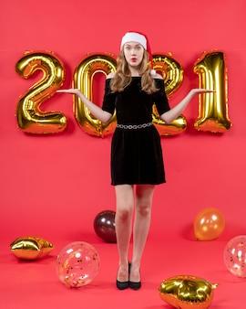 Vue de face jeune femme en robe noire ouvrant ses mains ballons sur rouge