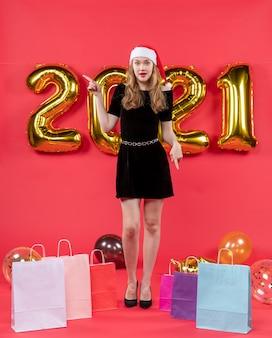 Vue de face jeune femme en robe noire pointant vers la gauche des sacs à provisions sur des ballons au sol sur rouge