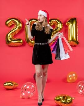 Vue de face jeune femme en robe noire pointant vers quelque chose tenant des ballons de sacs à provisions sur rouge