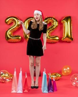 Vue de face jeune femme en robe noire pointant vers les sacs gauches sur les ballons au sol sur le rouge