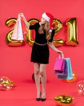 Vue de face jeune femme en robe noire regardant des ballons de sacs à provisions sur rouge