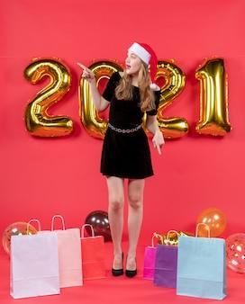 Vue de face jeune femme en robe noire regardant les sacs gauches sur les ballons au sol sur le rouge