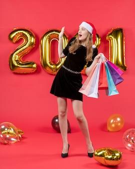 Vue de face jeune femme en robe noire saluant quelqu'un tenant des sacs à provisions ballons sur rouge