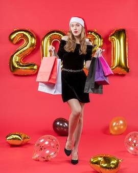 Vue de face jeune femme en robe noire tenant des ballons de sacs à provisions sur rouge