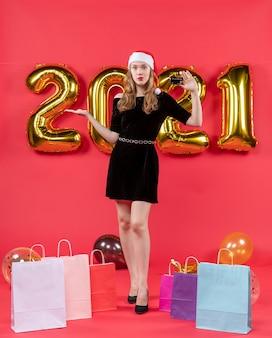 Vue de face jeune femme en robe noire tenant des sacs de cartes sur des ballons au sol sur rouge