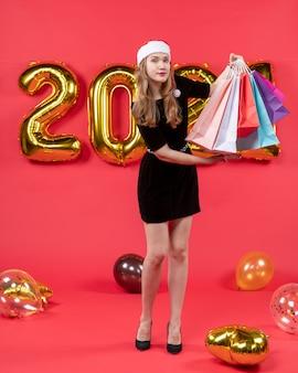 Vue de face jeune femme en robe noire tenant des sacs à provisions dans des ballons de mains sur rouge