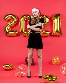 Vue de face jeune femme en robe noire traversant des ballons de mains sur rouge