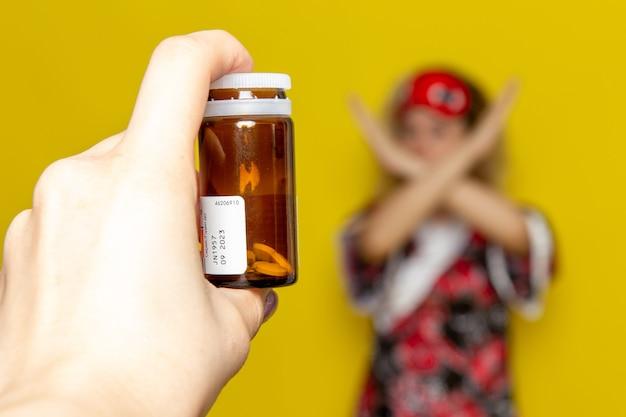Vue de face jeune femme en robe de nuit masque pour les yeux avec une main féminine concentrée tenant des pilules sur la ligne de front sur la couleur du modèle de lit de nuit de sommeil bureau jaune