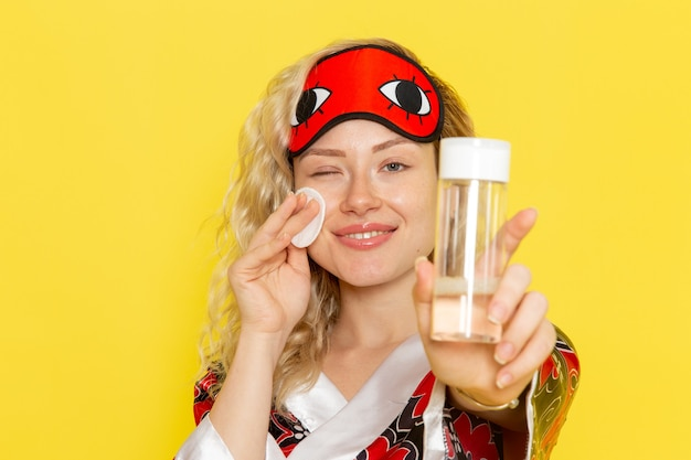Vue de face jeune femme en robe de nuit et portant un masque pour les yeux nettoyant son visage de maquillage sur le modèle de lit de nuit fille sommeil bureau jaune