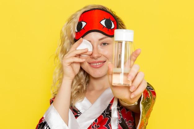 Vue de face jeune femme en robe de nuit et portant un masque pour les yeux nettoyant son visage de maquillage souriant sur le modèle de lit de nuit fille sommeil bureau jaune
