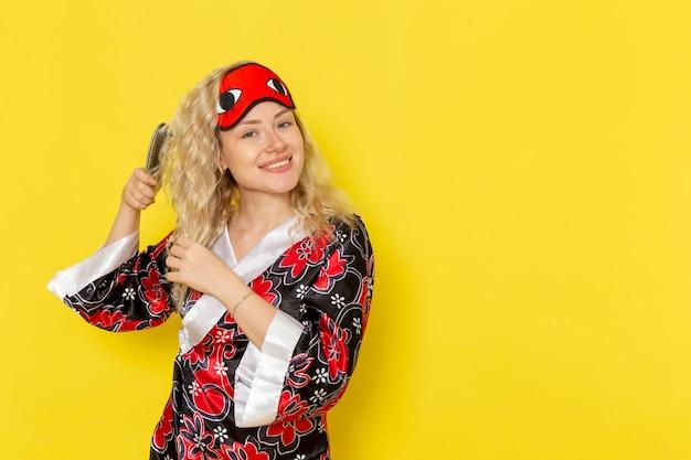 Vue de face jeune femme en robe de nuit et portant un masque pour les yeux se brosser les cheveux souriant sur le modèle de lit de nuit fille sommeil mur jaune