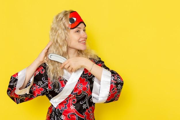 Vue de face jeune femme en robe de nuit et portant un masque pour les yeux se brosser les cheveux avec le sourire sur le modèle de lit de nuit fille sommeil mur jaune