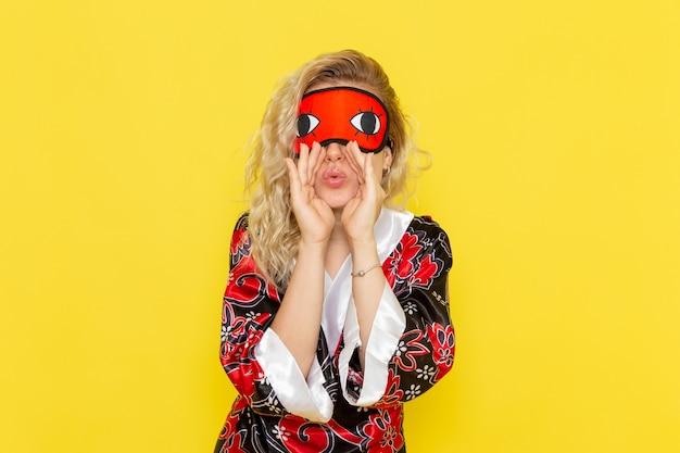 Vue de face jeune femme en robe de nuit et portant un masque pour les yeux se préparant à dormir appelant sur le mur jaune sommeil femme couleur obscurité nuit