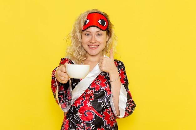 Vue de face jeune femme en robe de nuit et portant un masque pour les yeux se préparant à dormir en buvant du café sur un mur jaune clair sommeil modèle féminin lit