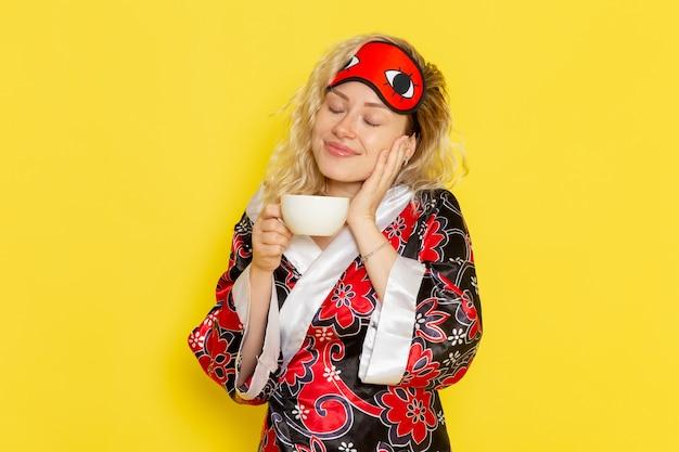 Vue de face jeune femme en robe de nuit et portant un masque pour les yeux se préparant à dormir en buvant du café souriant sur le mur jaune sommeil modèle féminin lit de nuit