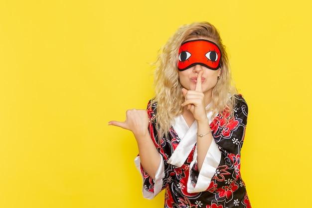 Vue de face jeune femme en robe de nuit et portant un masque pour les yeux se préparant à dormir demandant d'être calme sur le mur jaune nuit sommeil femelle couleur de l'obscurité
