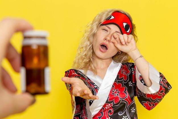 Vue de face jeune femme en robe de nuit et portant un masque pour les yeux se préparant à dormir demander des pilules sur un mur jaune clair sommeil modèle féminin lit de nuit