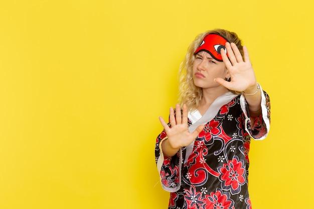 Vue de face jeune femme en robe de nuit et portant un masque pour les yeux se préparant à dormir mécontent sur mur jaune clair sommeil modèle féminin lit de nuit