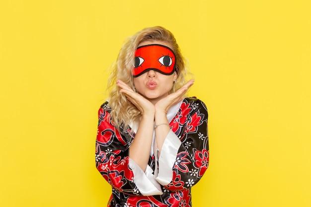 Vue de face jeune femme en robe de nuit et portant un masque pour les yeux se préparant à dormir mignon posant sur mur jaune sommeil femme couleur obscurité nuit