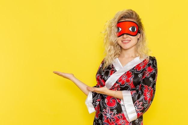 Vue de face jeune femme en robe de nuit et portant un masque pour les yeux se préparant à dormir souriant sur le mur jaune nuit sommeil femelle couleur obscurité