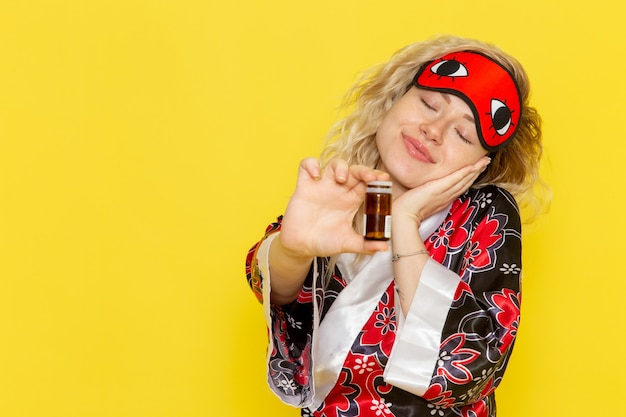 Vue de face jeune femme en robe de nuit et portant un masque pour les yeux se préparant à dormir tenant des pilules sur le bureau jaune nuit modèle de l'obscurité féminine