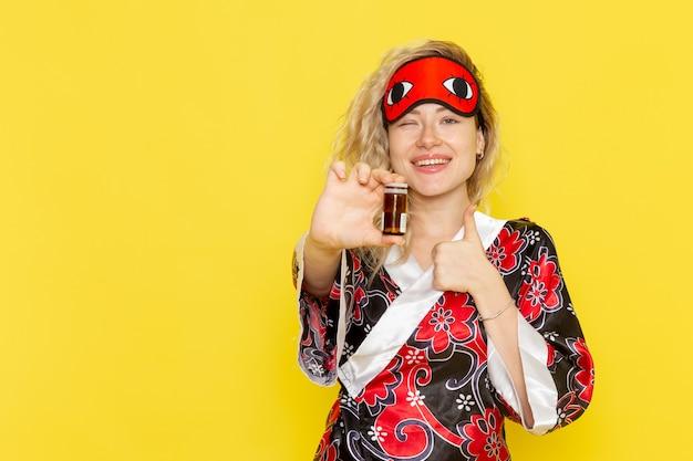 Vue de face jeune femme en robe de nuit et portant un masque pour les yeux se préparant à dormir tenant des pilules sur le mur jaune sommeil nuit modèle femme obscurité