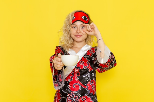 Vue de face jeune femme en robe de nuit et portant un masque pour les yeux se préparant à dormir tenant une tasse de café sur le mur jaune sommeil fille nuit modèle de lit