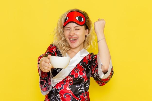 Vue de face jeune femme en robe de nuit et portant un masque pour les yeux se préparant à dormir tenant une tasse de café sur le mur jaune sommeil modèle féminin lit de nuit