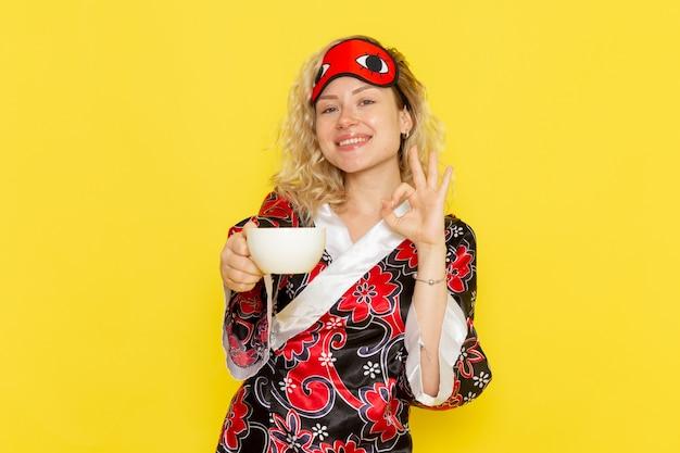 Vue de face jeune femme en robe de nuit et portant un masque pour les yeux se préparant à dormir tenant une tasse de café souriant sur un mur jaune sommeil modèle féminin lit de nuit