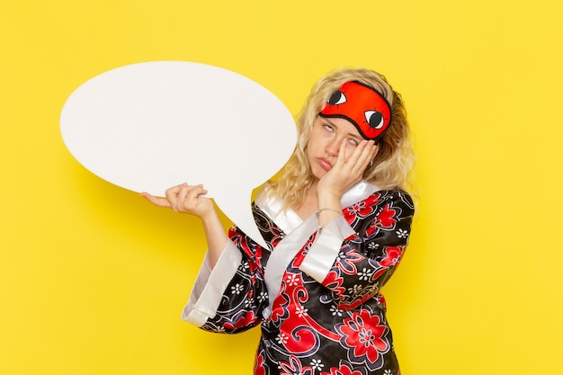 Vue de face jeune femme en robe de nuit et portant un masque pour les yeux tenant un énorme panneau blanc sur le bureau jaune sommeil nuit modèle fille couleur