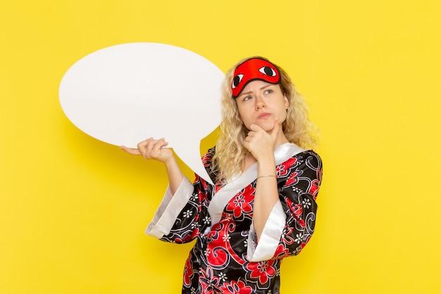 Vue de face jeune femme en robe de nuit et portant un masque pour les yeux tenant un énorme panneau blanc pensant sur le mur jaune sommeil nuit modèle fille couleur