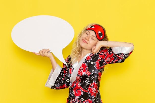 Vue de face jeune femme en robe de nuit et portant un masque pour les yeux tenant grand panneau blanc sur le mur jaune sommeil nuit modèle fille couleur