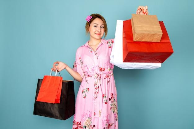 Une vue de face jeune femme en robe rose conçue de fleurs tenant des paquets d'achat et souriant sur bleu
