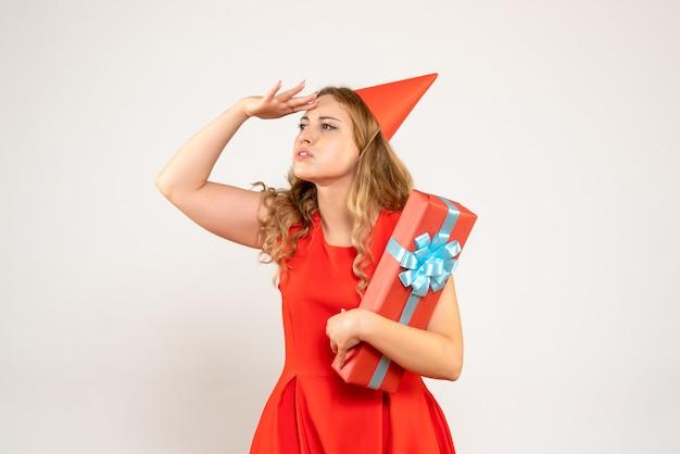 Vue de face jeune femme en robe rouge célébrant noël avec présent