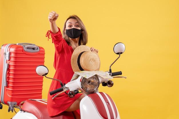 Vue de face jeune femme en robe rouge sur cyclomoteur levant la main