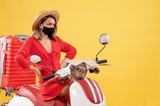 Vue de face jeune femme en robe rouge sur un cyclomoteur mettant les mains sur une taille