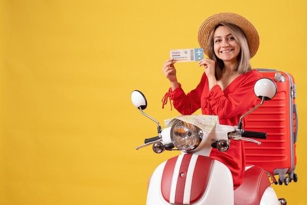 Vue de face jeune femme en robe rouge sur un cyclomoteur avec une valise rouge tenant un billet