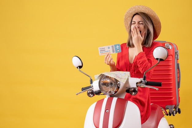 Vue de face jeune femme en robe rouge tenant un billet en bâillant sur un cyclomoteur