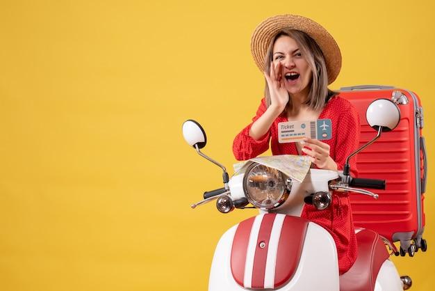 Vue de face jeune femme en robe rouge tenant un billet criant sur un cyclomoteur