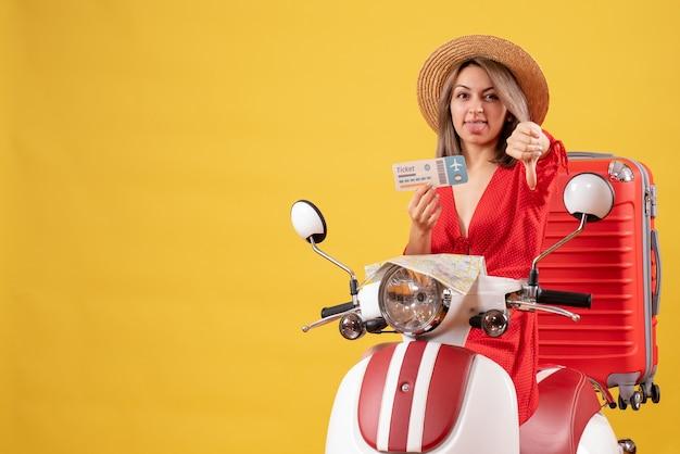 Vue de face jeune femme en robe rouge tenant un billet donnant le pouce vers le bas sur un cyclomoteur