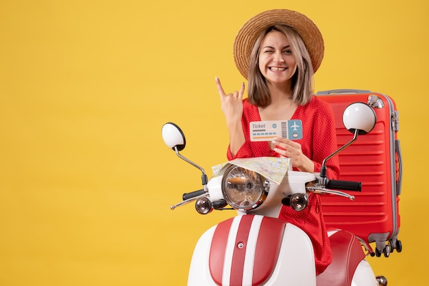 Vue de face jeune femme en robe rouge tenant un billet faisant un signe de roche sur un cyclomoteur