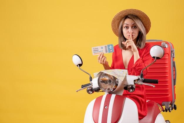 Vue de face jeune femme en robe rouge tenant un billet faisant signe de silence sur un cyclomoteur