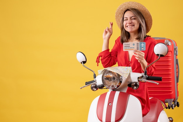 Vue de face jeune femme en robe rouge tenant un billet faisant signe de souhait sur cyclomoteur