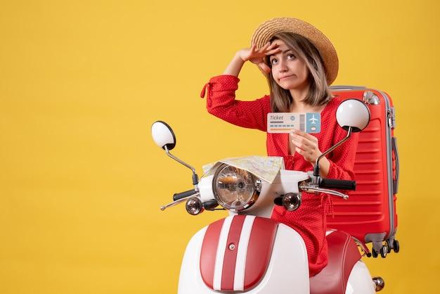 Vue de face jeune femme en robe rouge tenant un billet observant sur un cyclomoteur