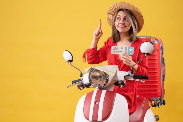 Vue de face jeune femme en robe rouge tenant un billet pointant le doigt vers le haut sur un cyclomoteur