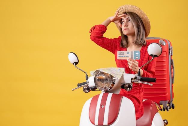 Vue de face jeune femme en robe rouge tenant un billet regardant quelque chose sur un cyclomoteur