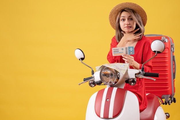 Vue de face jeune femme en robe rouge tenant un billet tenant sa gorge sur un cyclomoteur