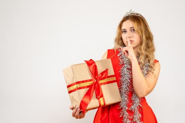 Vue de face jeune femme en robe rouge tenant le cadeau de noël