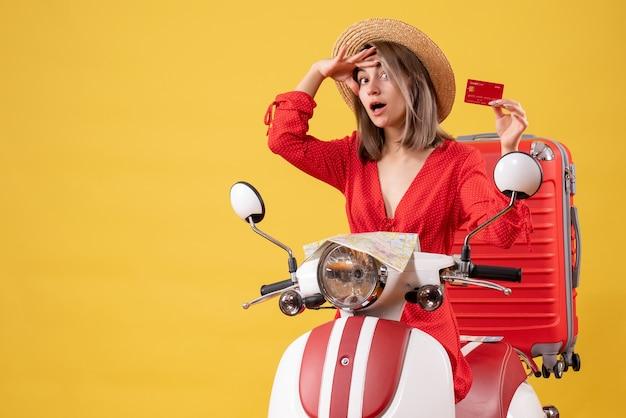 Vue de face jeune femme en robe rouge tenant une carte bancaire sur un cyclomoteur