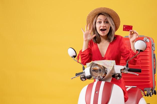 Vue de face jeune femme en robe rouge tenant une carte de crédit en agitant la main près d'un cyclomoteur